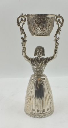 A SILVER WAGER CUP, cast as a lady, her full skirt being one of the cups, she holds aloft a smaller rotating cup (based on a German 16th century design, sometimes referred to as Marriage or Wedding cups), the main section hallmarked Birmingham 1977, the small cup Sheffield 1977, both made by Barrowcliff Silvercraft, 19cm high, 388g.