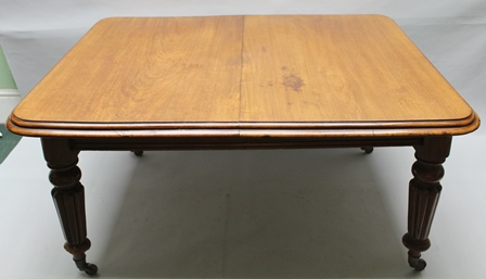 A VICTORIAN MAHOGANY WIND-OUT DINING TABLE, raised on turned and fluted supports with castors, complete with two leaves and winding handle, 120cm x 148cm (extending to 236cm)