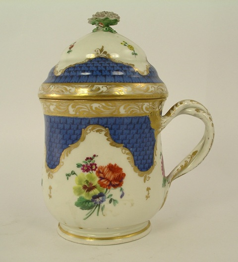 AN AUSTRIAN PORCELAIN MUG and cover decorated in polychrome with flora and highlighted with gilt, overlapped two strung handle, 18cm high
