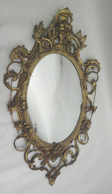 A 19TH CENTURY CHIPPENDALE STYLE ROCOCO CARVED GILT WOOD AND GESSO MIRROR having highly ornate scroll foliate and floral wired surround and period oval plain plate, 1.45cm x 80cm overall,  bears trade label John Doonan Carver & Gilder, Glasgow