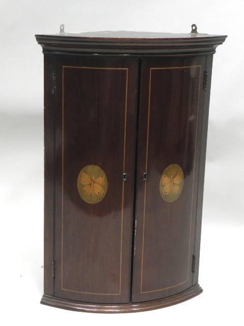 AN EDWARDIAN/1920'S MAHOGANY BOW FRONTED HANGING CORNER CUPBOARD, having moulded pediment, boxwood strung doors with oval butterfly decoration enclosing two shaped shelves, 69cm x 48cm
