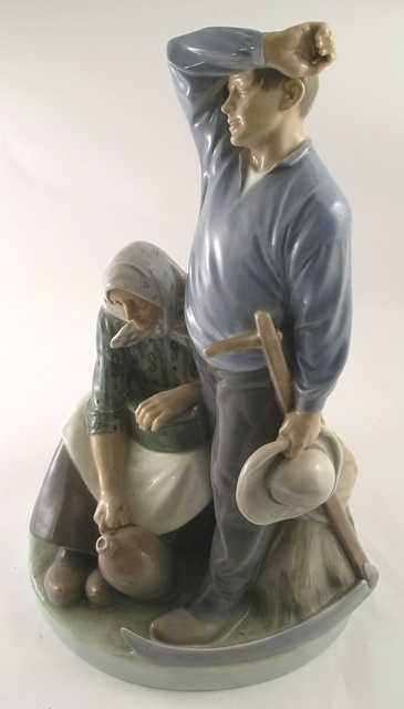 A ROYAL COPENHAGEN PORCELAIN GROUP OF AN AGRICULTURAL LABOURER, standing, wiping his brow, and a seated woman beside in clogs, 52cm high