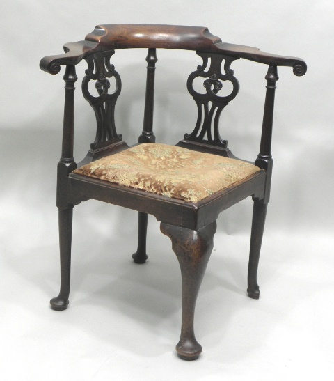 A LATE GEORGE III MAHOGANY CORNER CHAIR having a shaped crest rail with scrolled arms, twin vase shaped pierced fretted splat with turned uprights, upholstered drop-in seat, raised on a single cabriole foreleg with flank tapered legs and pad feet