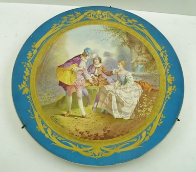 A SEVRES STYLE CERAMIC WALL PLATE, having gilded blue ground rim, to the centre a scene of lovers in 18th century costume in a Parkland setting, signed E. Grisard, 37cm diameter