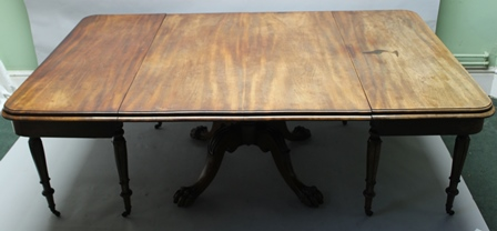 A 19TH CENTURY MAHOGANY DINING TABLE comprising two end sections on turned and fluted supports, a large central panel sits upon a turned stem and four paw feet supports, there are two moulded end sections which turn the central section into a breakfast table, the end sections can function as side tables, 134cm x 214cm