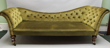A VICTORIAN BUTTON BACK SOFA with scrolling ends, the one side higher, in the manner of a chaise longue, green fabric upholstered, raised on carved mahogany feet with brass castors
