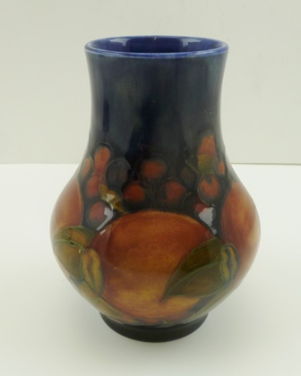 A MOORCROFT POMEGRANATE PATTERN POTTERY VASE of baluster form, with tube lined and painted decoration on a dark blue ground, impressed factory marks to base, 12cm high