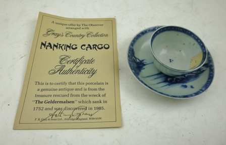 AN 18TH CENTURY CHINESE NANKING PORCELAIN TEA BOWL AND SAUCER, having cobalt blue painted landscape decoration, bears paper labels from the Nanking Cargo Auction at Christies, together with a certificate, saying from the wrecked ship The Geldermalsen, which sank in 1752 and discovered in 1985, saucer 10cm diameter, bowl 6.3cm diameter