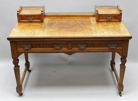 A LATE 19TH CENTURY WALNUT DESK, having two-drawer upstand with brass gallery back, boxwood strung writing area, over two in-line drawers, supported on substantial turned and blocked legs with single stretcher between, the whole supported on period brass castors, 89cm x 122cm