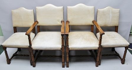 A SET OF EIGHT BRIGHTS OF NETTLEBED OAK FRAMED DINING CHAIRS, having cream leather studded upholstery, comprising a pair of open arm chairs and six singles (8)