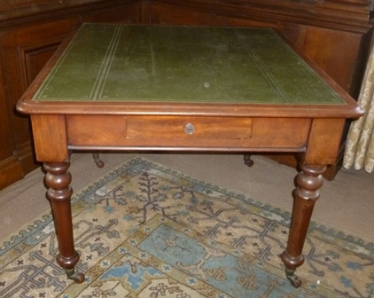 A 19TH CENTURY MAHOGANY LIBRARY TABLE, having green leather inset top, frieze fitted single drawer, raised on ring turned supports with castors, 100cm x 107cm