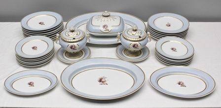 A FLIGHT BARR & BARR WORCESTER PART DINNER SERVICE circa 1815-1820, comprising;- large oval meat serving platter 50cm, smaller platter 40.5cm, one of 31.5cm and 25.5cm, a rectangular tureen and cover, a pair of sauce tureens with covers and bases, 11 plates 21cm diameter and 13 plates 25cm diameter, blue/grey border, gilt lined, with central hand painted floral cornucopia crest, impressed mark FBB believed to be the crest of the Lely family of Framingham Hall, Norfolk (lot comes with a cornucopia livery button)