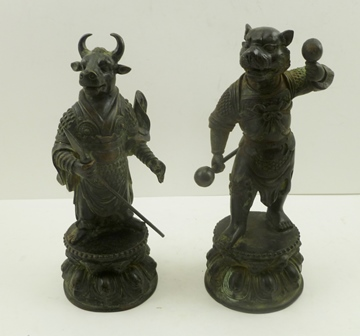A PAIR OF 19TH CENTURY BRONZE TIBETAN TEMPLE GUARDIANS OF ZOOMORPHIC FORM, both in armour, one with a bulls head, the other a dogs head, standing upon Lotus plinths, 24cm high