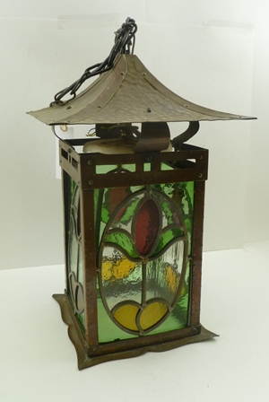 AN ARTS & CRAFTS DESIGN HALL LANTERN, having beaten copper frame with leaded glass panels to four sides, pagoda roof, with chain suspension and ceiling rose, 38cm high