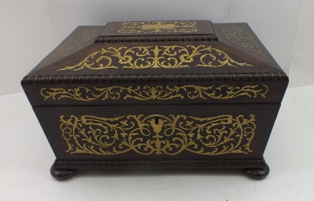 A 19TH CENTURY ROSEWOOD SEWING BOX, decoratively brass inlaid, fitted ring handles to the sides, hinged cover opens to reveal fabric lined interior with compartmentalised tray, raised on bun feet, 30cm wide