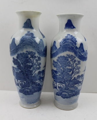 A PAIR OF CHINESE PORCELAIN VASES of baluster form, having cobalt blue transfer mountain landscape decoration with lines of character text in homage to Ming, 25cm high, each with a fabric covered box