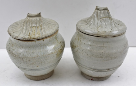 A PAIR OF CHINESE SONG DYNASTY LIDDED JARS, of baluster form with pagoda roof form covers, in a grey/green glaze, 10cm high