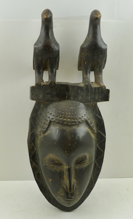 AN EARLY TO MID 20TH CENTURY IVORY COAST BAULE YUARE CARVED WOOD MASK, ebonised finish with a crest of two perched birds, 48cm high