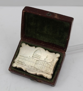 JOHN TONGUE AN EARLY VICTORIAN SILVER GILT VINAIGRETTE, the cover engraved with an image of St. Pauls Cathedral, base with acanthus scrolls, internal pierced grille, Birmingham 1842, 4cm wide 24g., in original leather covered outer case with greenvelvet lining