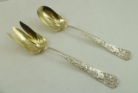 A PAIR OF TIFFANY STERLING SILVER SALAD SERVERS, having cast fruiting vine handles, gilded bowls, date relates to 1873-1880, 241g.