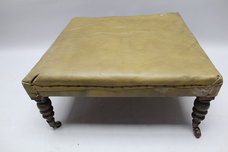 A 19TH CENTURY LOW SQUARE FOOTSTOOL, upholstered in green leather, having ring turned mahogany supports with brass casters, 72cm square