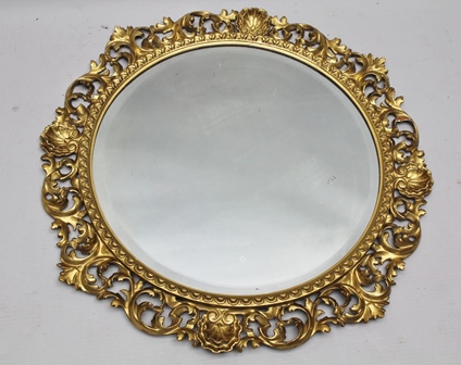 A 20TH CENTURY FLORENTINE DESIGN CIRCULAR CARVED GILDED WOOD FRAME with scallops and scrolling acanthus leaves, inset a bevel plate mirror, 51cm diameter