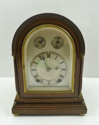 AN EDWARDIAN MAHOGANY CASED CHIMING MANTEL CLOCK, having arch top case, raised on brass bun feet, silvered dial with Roman numerals, a chime/silent selector and speed regulator to the top of arch, 8-day chiming movement, 22.5cm high