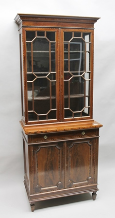 A REGENCY DESIGN MAHOGANY BOOKCASE CABINET, having crossbanded and string inlaid top, fitted two astragal glazed doors, over a base fitted with a single drawer with brass ring handles and two cupboard doors, below on spade feet, 81cm wide x 188cm high