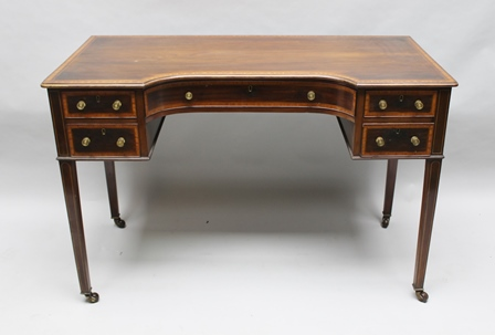 A LATE VICTORIAN MAHOGANY SATINWOOD CROSSBANDED WRITING DESK, having central concave drawer flanked by two smaller drawers on either side with brass knob handles, raised on squared tapering supports with castors, 113cm wide