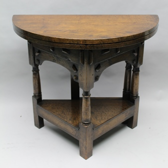 A JACOBEAN DESIGN OAK TABLE having demi-lune foldover top, turns a side table via a gateleg action into a circular occasional table, decorative frieze, on turned supports, with triangular under tier, 85cm wide