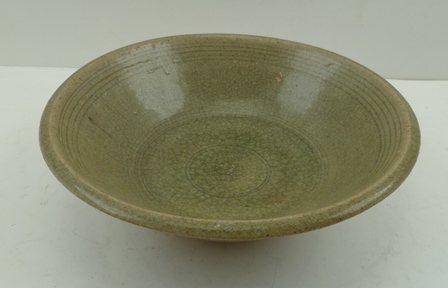 A CHINESE CELADON BOWL, possibly Sang/Longquan, having incised line decoration to the inner rim and concentric circles to the sole, 22.5cm diameter