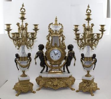 A LOUIS XIV DESIGN GARNITURE MANTEL CLOCK SET comprising; a central lyre form clock with faun mounts and urn finial, in white marble and cast gilt metal, raised on outswept paw front feet, 63cm high, together with a pair of six branch seven light matching candelabras