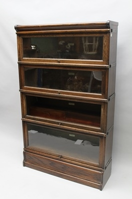 A GLOBE-WERNICKE OAK FOUR TIER GLASS FRONTED BOOKCASE of typical form and construction, 142cm x 87cm