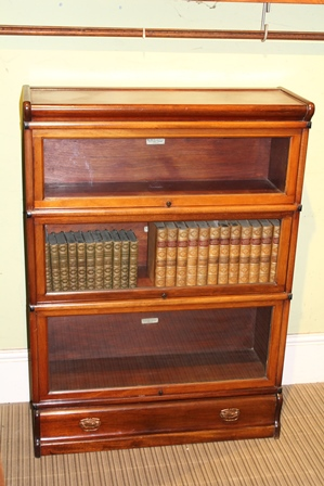 A GLOBE-WERNICKE BRANDED THREE TIER MAHOGANY GLASS FRONT BOOKCASE the plinth section having single full width drawer, 120cm x 87cm