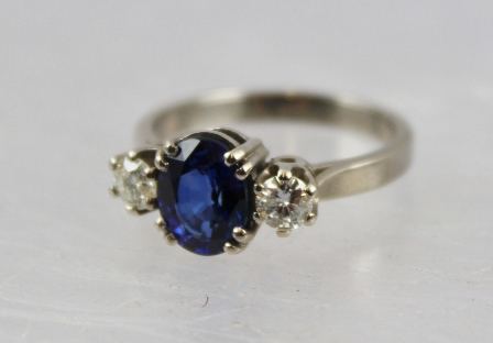 A SAPPHIRE & DIAMOND THREE STONE RING having oval central stone flanked by twin brilliants, in a white gold coloured metal claw setting, un-marked, tests 18ct, size N