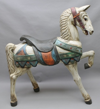 A LATE 20TH CENTURY DECORATIVE CARVED HARDWOOD HORSE, polychrome over-painted, white bodied with polychrome girdles and saddle, standing three square with left foreleg raised, and probably imported from Eastern lands 151cm high to ear tip 142cm in length (fully dismantled for ease of transportation)