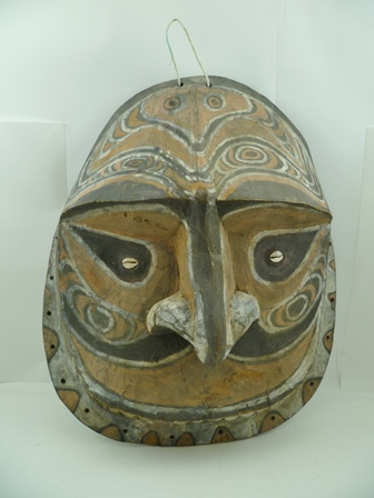 A PACIFIC OCEAN PAPUAN TRIBAL MASK, carved wood polychrome painted in colours of amber, white and chocolate brown, considered to be from an early Pacific tribe, circa 1910, from a Colonial English collection, 53cm x 44cm