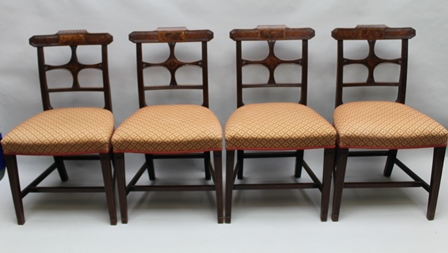 A SET OF FOUR 19TH CENTURY POSSIBLY SCOTTISH MAHOGANY DINING CHAIRS with decorative crest rail over X shaped back, with reeded side supports and four legs, with over stuffed seat pad and plain H shaped stretcher between 89cm high