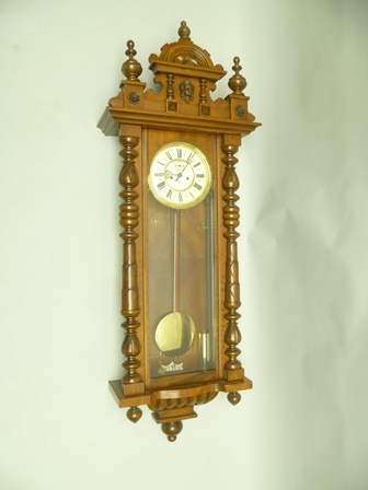 AN EARLY 20TH CENTURY GUSTAV BECKER VIENNESE STYLE HANGING WALL CLOCK of typical form and construction with fancy crest and pilaster sides, finished in walnut, with keys weights and display pendulum, 134cm high overall
