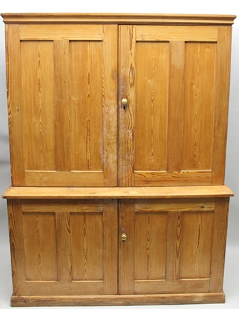 A LATE 19TH CENTURY PITCH PINE HOUSEKEEPERS CUPBOARD having twin plain panelled upper doors, opening to reveal a shelved interior, supported on a deeper base, also with two plain panelled doors and shelved interior, the whole on a shallow plinth base 184cm high x 141cm wide