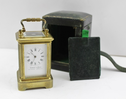 A LATE VICTORIAN MINIATURE CARRIAGE CLOCK, brass frame with bevelled glass, white enamel dial with Roman numerals, inscribed Edwards & Jones 161 Regent Street, complete with leather case with key, 7.5cm high