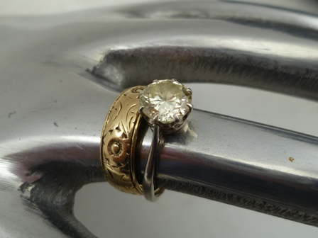 A DIAMOND SOLITAIRE RING, brilliant cut, on unmarked band, possibly white gold or platinum, stone is considered to be in the region of 1 carat, ring size L, together with a 9CT GOLD WEDDING BAND with floral chased decoration, size K and half