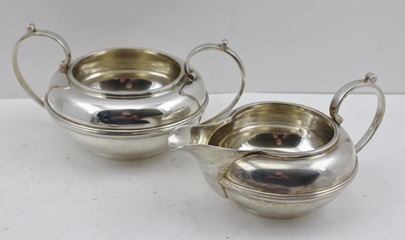 NAYLER BROTHERS A SILVER MILK JUG AND A TWO-HANDLED SUGAR BOWL, of squat bun form with moulded line detail, London 1927, engraved also R M Halford & Sons, combined weight 573g