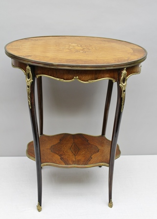 A PROBABLE 19TH CENTURY FRENCH BRASS BOUND OCCASIONAL TABLE having kingwood and floral inlaid central motif, rosewood banding, having profusely applied metal moulding supported on four slender legs united by a quarter veneered rosewood undertier, 73cm high