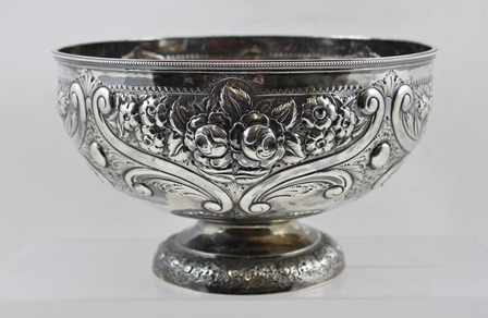 HENRY WILKINSON AND CO. A LATE VICTORIAN SILVER ROSE BOWL having floral embossed decoration, raised on a circular platform foot, London 1893, 25cm diameter, 779g