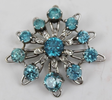 A STAR FORM BROOCH SET BLUE ZIRCONS on a white metal frame, considered to be 18ct white gold, 5cm across