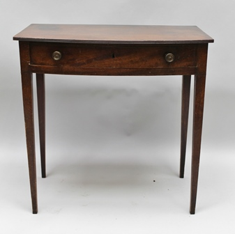 A LATE GEORGIAN MAHOGANY BOW FRONT SIDE TABLE, having plain top with reeded edge, single full width drawer, supported on plain square tapering legs 77cm x 76cm