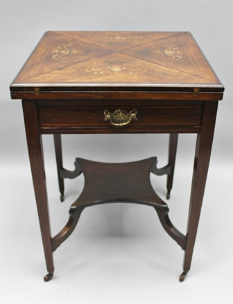 A LATE 19TH/ EARLY 20TH CENTURY INLAID ENVELOPE TOPPED CARD TABLE, finished in rosewood, fitted a single drawer, supported on four square tapering legs, united by an under tier, with ceramic castors, 74cm high