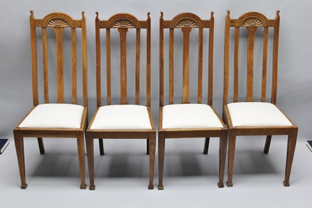 A SET OF FOUR ENGLISH ARTS & CRAFTS DESIGN OAK SLAT BACK HIGH DINING CHAIRS each with carved crest rail, and upholstered drop-in seat pad, on plain square form legs, 109cm high