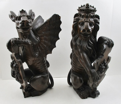 A PAIR OF 19TH CENTURY CARVED OAK NEWEL POST MOUNTS, Heraldic beasts, one in the form of a seated lion holding a crested shield of a crowned harp, the other a gryphon with a shield crested with a crowned rose, 42cm high